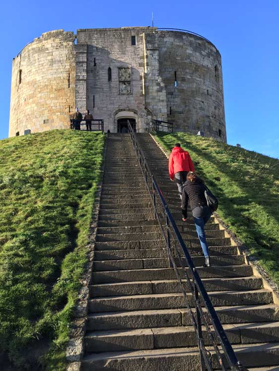 people climbing Cliffords Tower in York