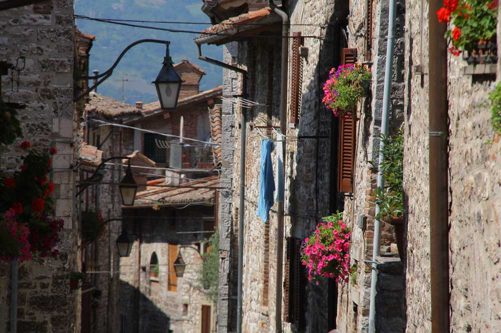 Umbria street scene with stone walls and flowers