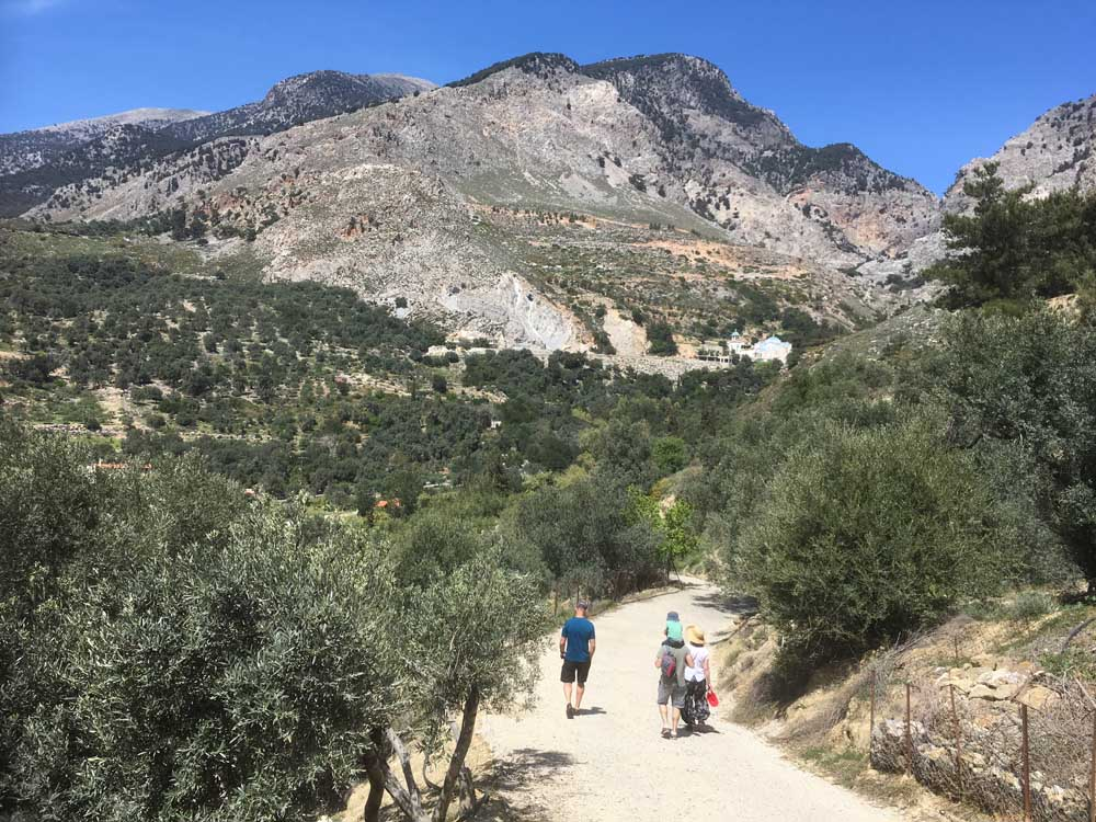 people walking along a track through olive groves and mountains in Crete with kids