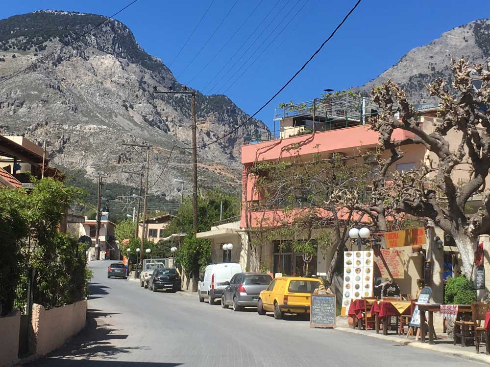 Zaros Crete mountain town with shops and cars
