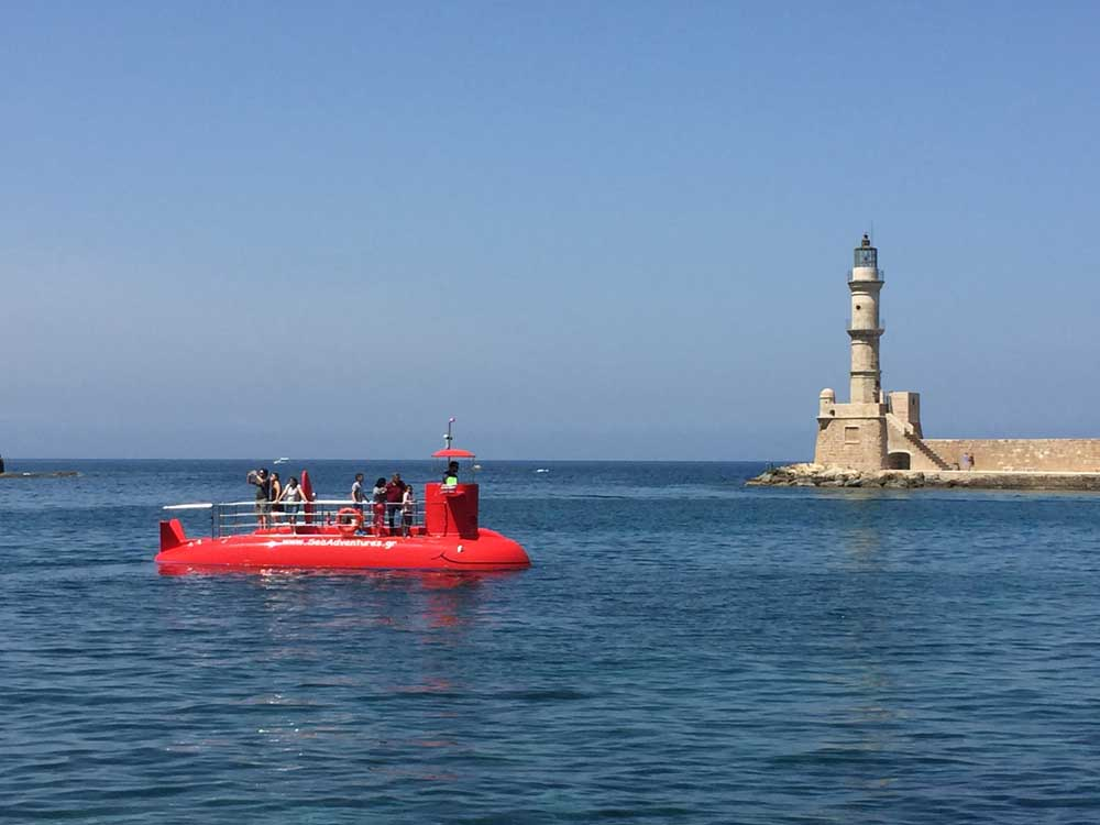 Crete with kids: our red submarine passing Chania's lighthouse