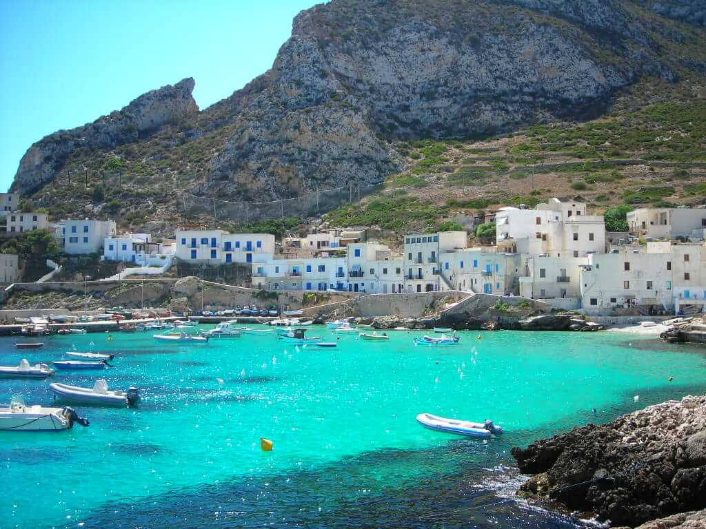 Seaside village with mountains in the background Favignana Sicily beaches