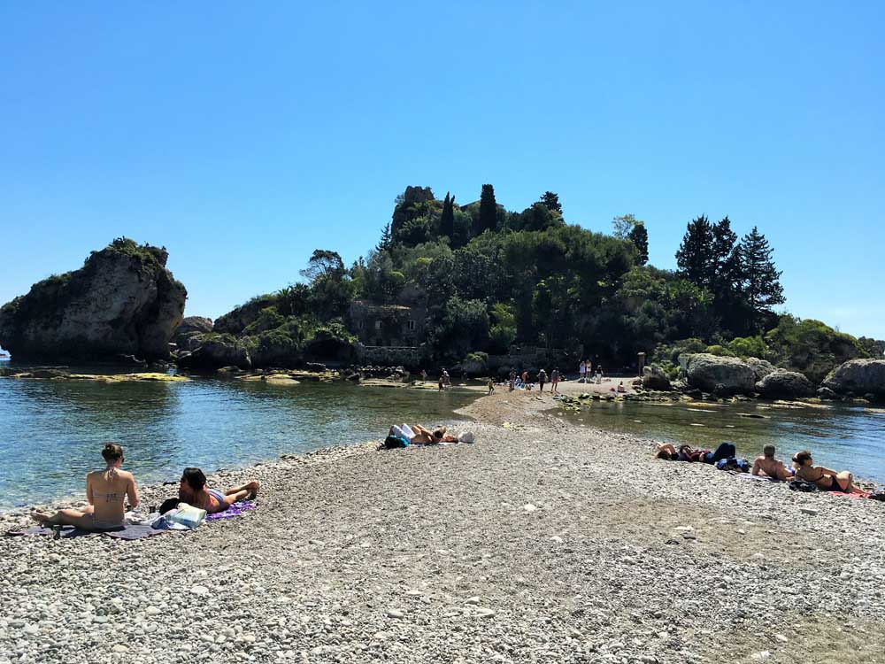 People lying on pebbly beach at Isola Bella Taormina Sicily