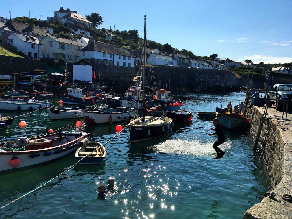 children jumping into the sea at Coverack Harbour Lizard Peninsula