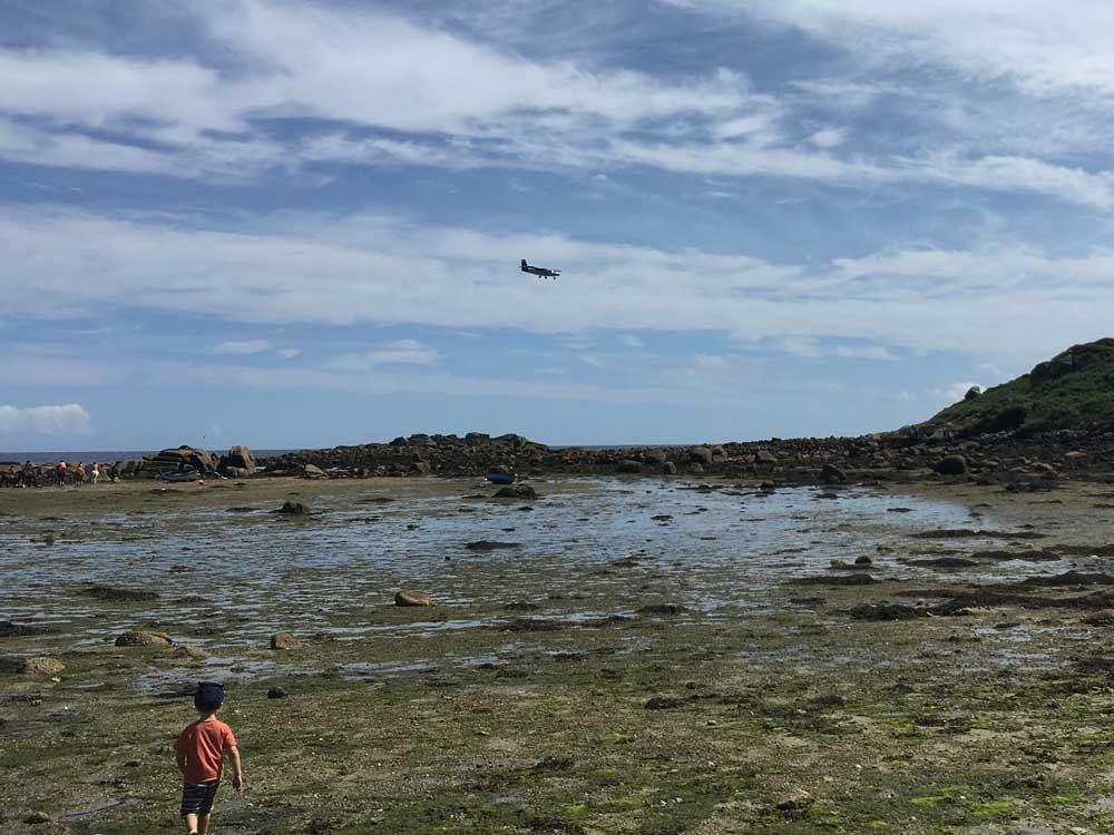 child walking on rocky beach with plane coming into land, scilly isles family holiday