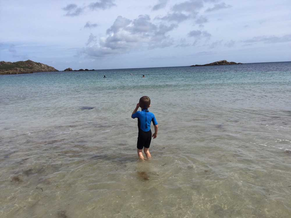 child paddling in the sea, Scilly isles family holiday