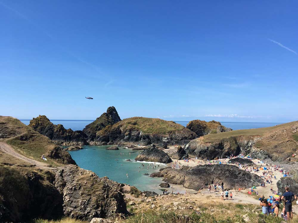 circular bay of Kynance Cove surrounded by grassy cliffs and blue sky, Lizard Peninsula Cornwall