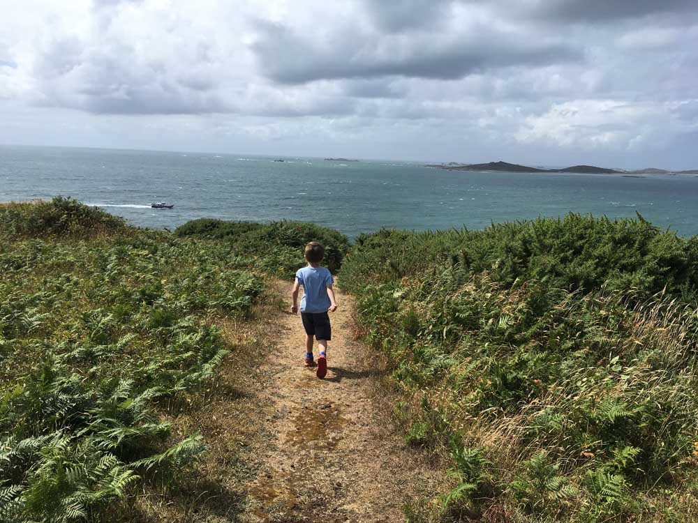 Child running along pathway overlooking the sea, Scilly Isles family holidays