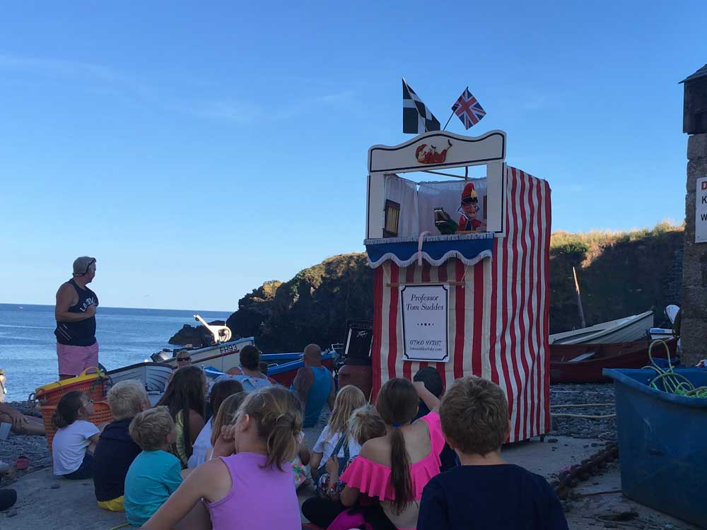 Children sitting on a pebbly beach to watch BBQ night at Cadgwith Cove