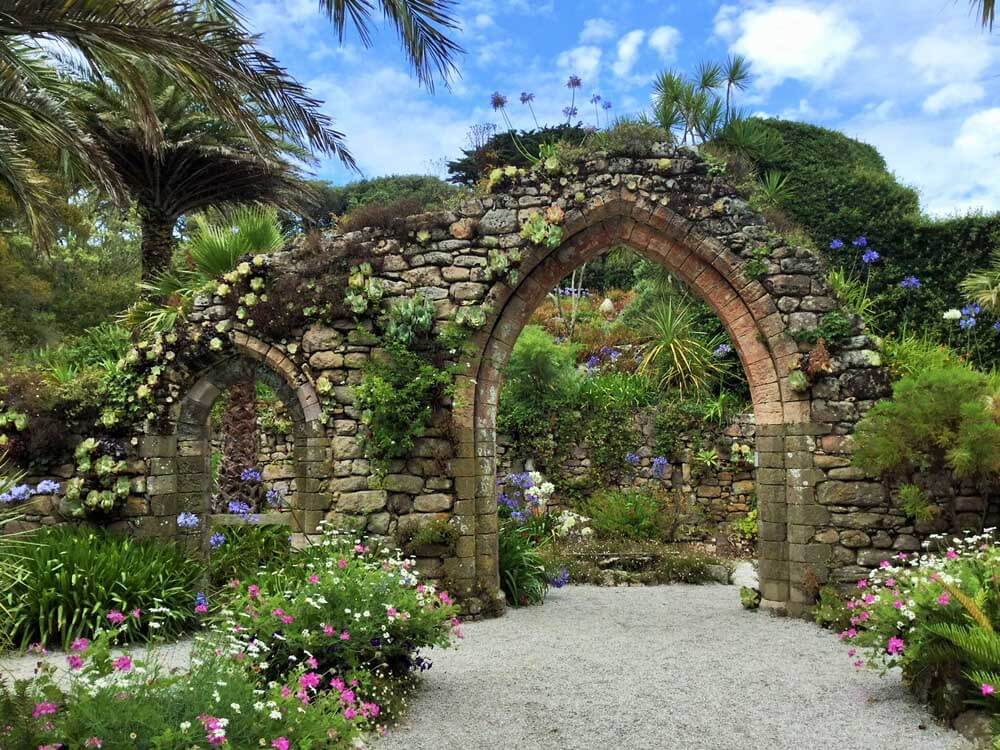 Archway surrounded by flowers in Tresco Abbey Gardens