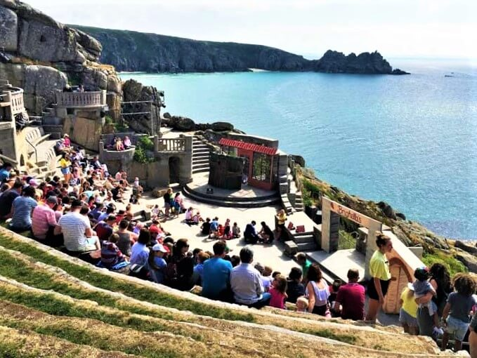 audience watching outdoor theatre in Cornwall with view of Atlantic Ocean