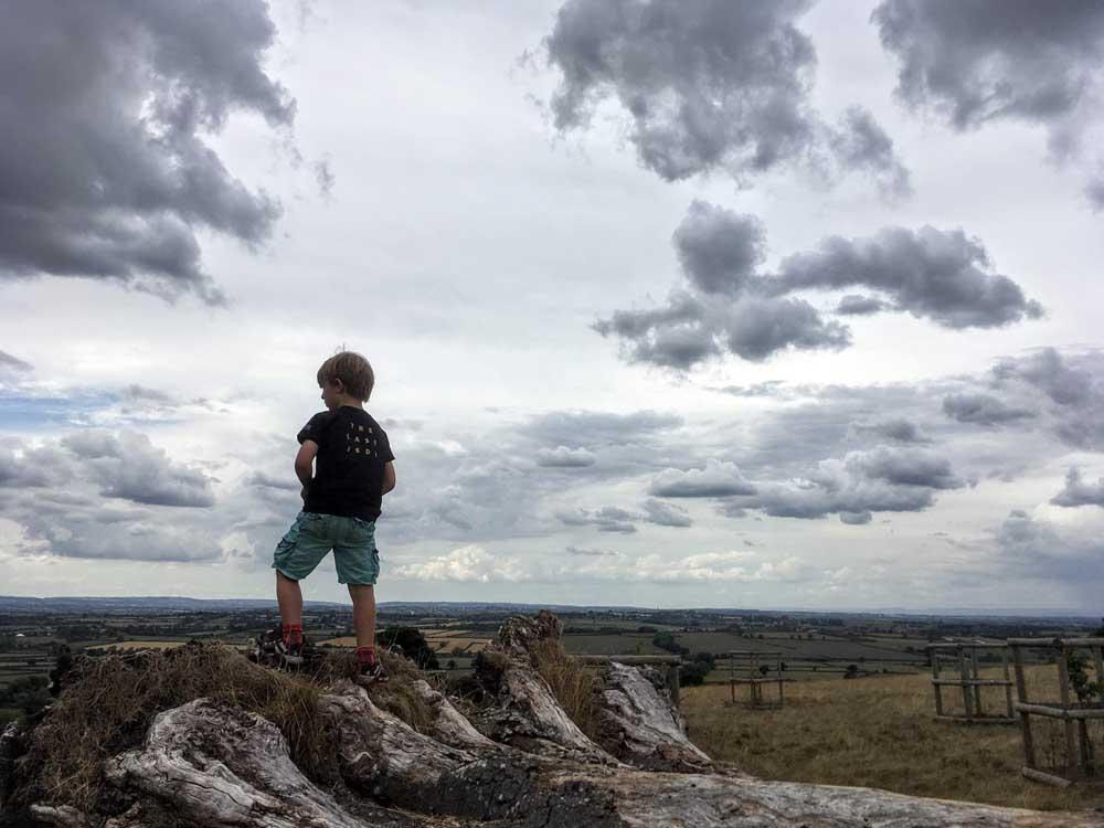 boy standing on rock overlooking Dyrham Park