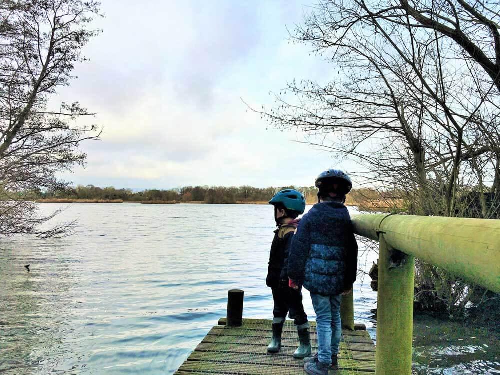 Children standing on pontoon at Fleet Pond, just off the M3 motorway