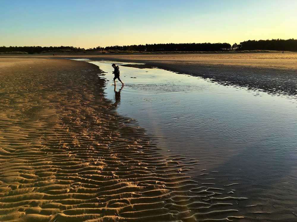 boy paddling holkham beach north norfolk short break