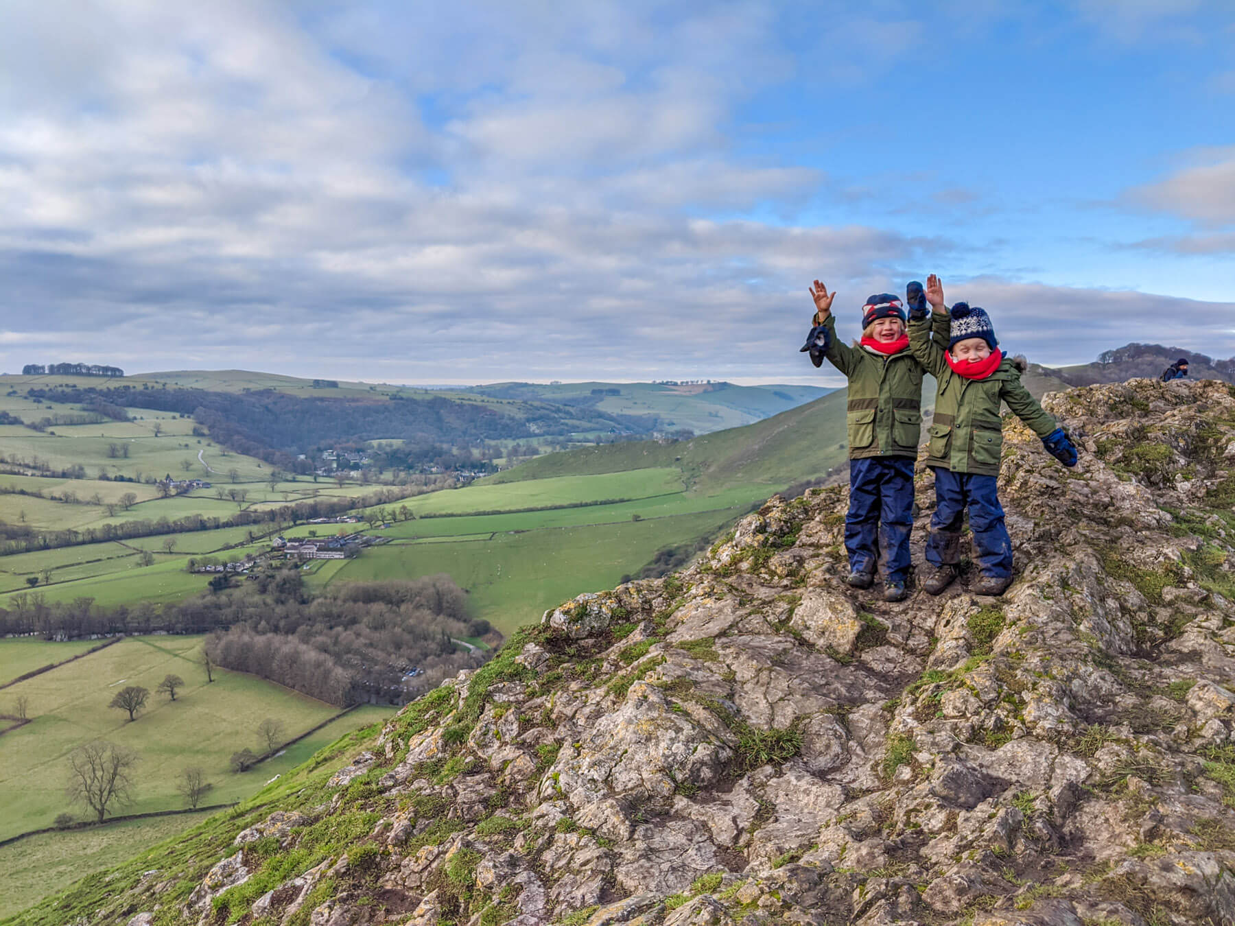 children standing on rocks with rural landscape of peak district
