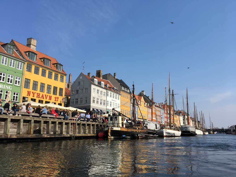 Colourful buildings and boats in harbour at Nyhavn Copenhagen Denmark