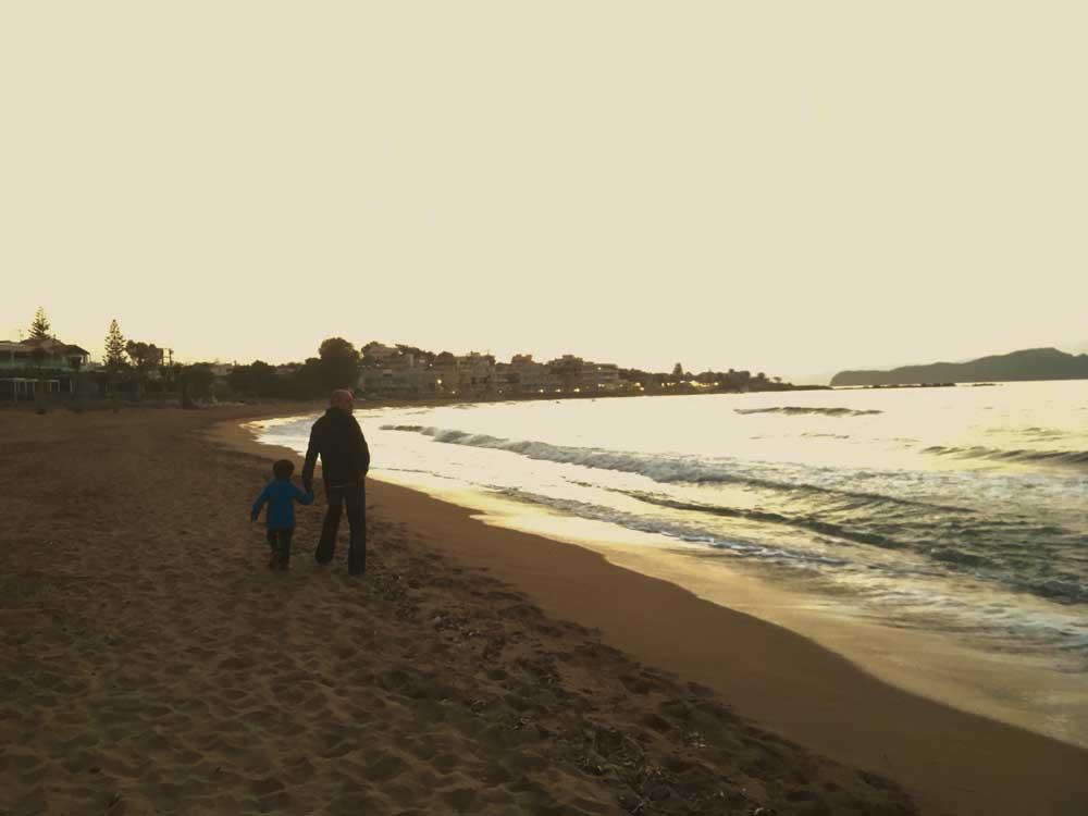 Family walking along sandy beach in crete