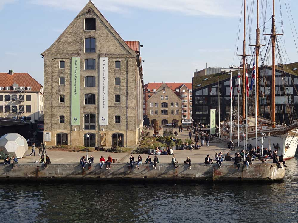 people sitting on the harbour in copenhagen denmark