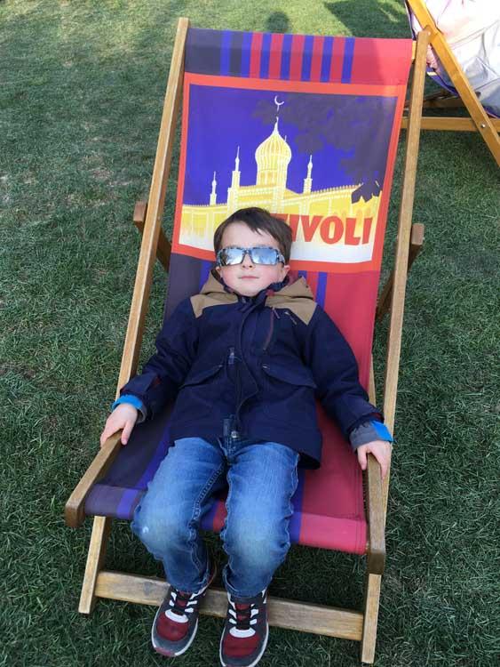 Child on deck chair at Tivoli gardens in Copenhagen