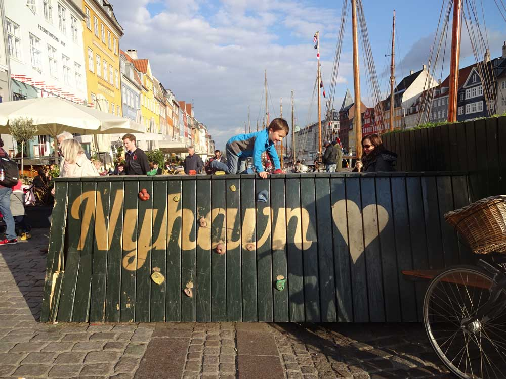 Child climbing on Nyhavn sign in Copenhagen Denmark