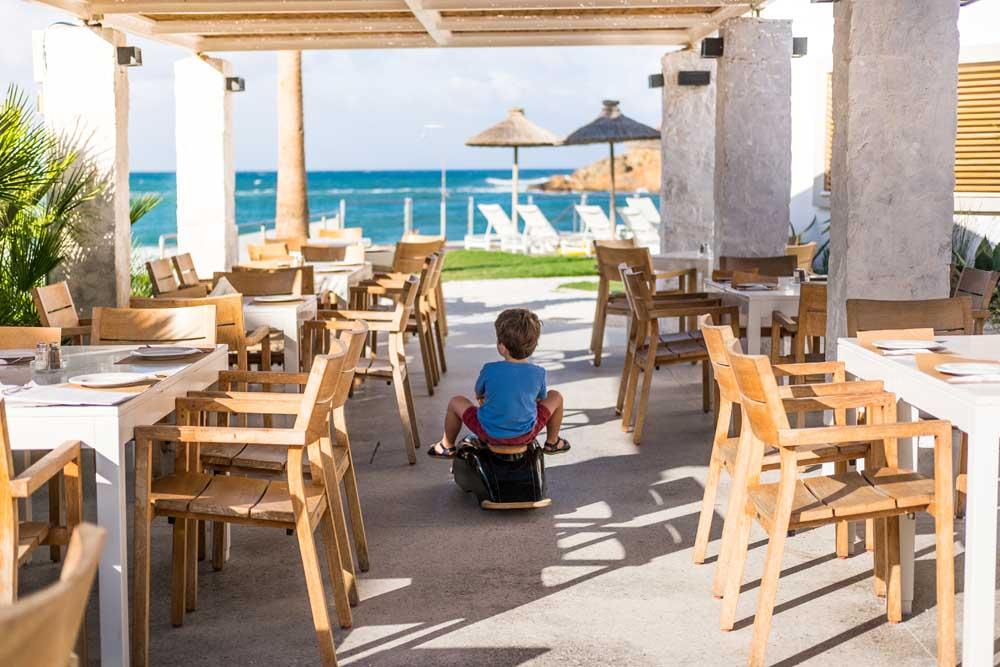 boy riding on toy in beachfront restaurant