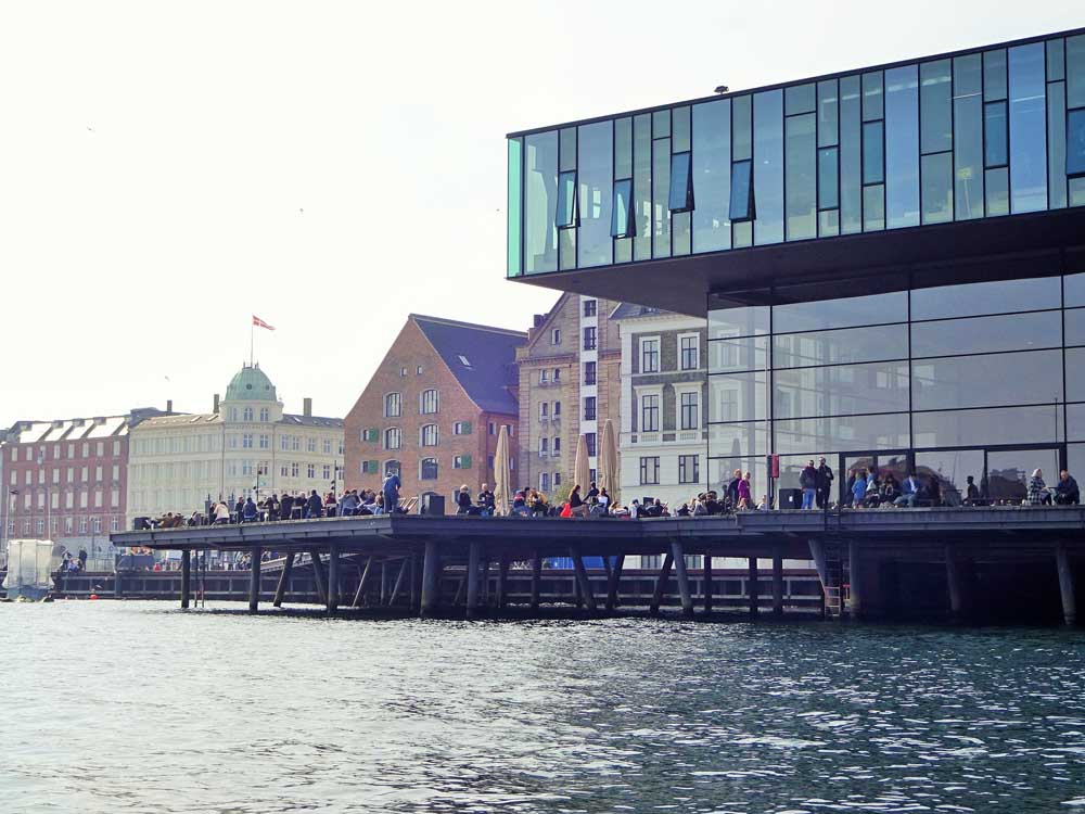 people sitting by the harbour in Copenhagen Denmark