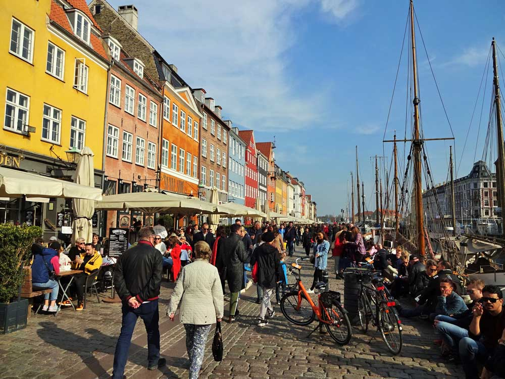 people walking next to colourful buildings of Nyhavn Copenhagen