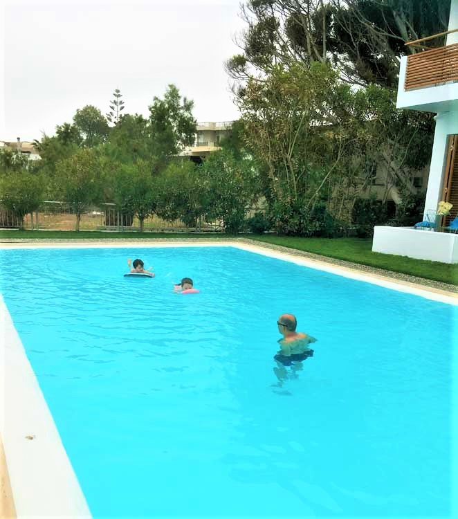 Family playing in a swimming pool in crete greece