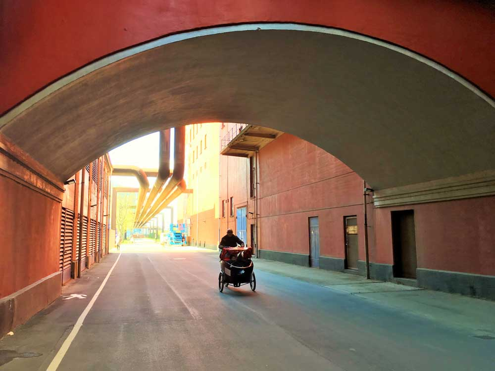 family cycling under an archway of a building in copenhagen denmark
