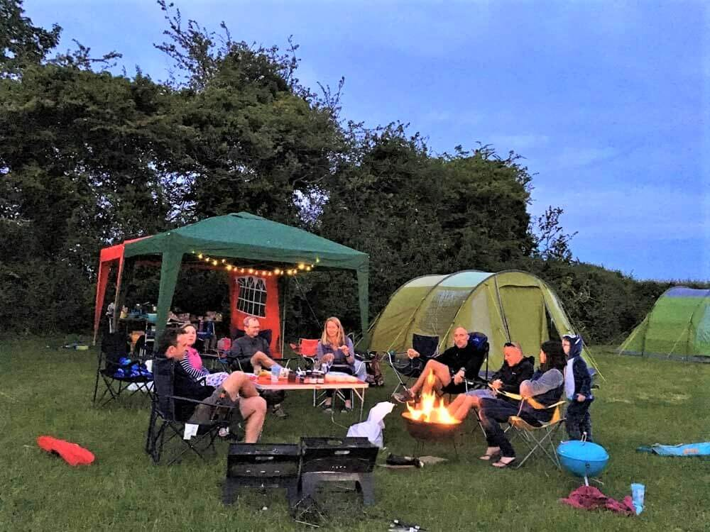 Group of people sat around campfire in Cotswolds campsite