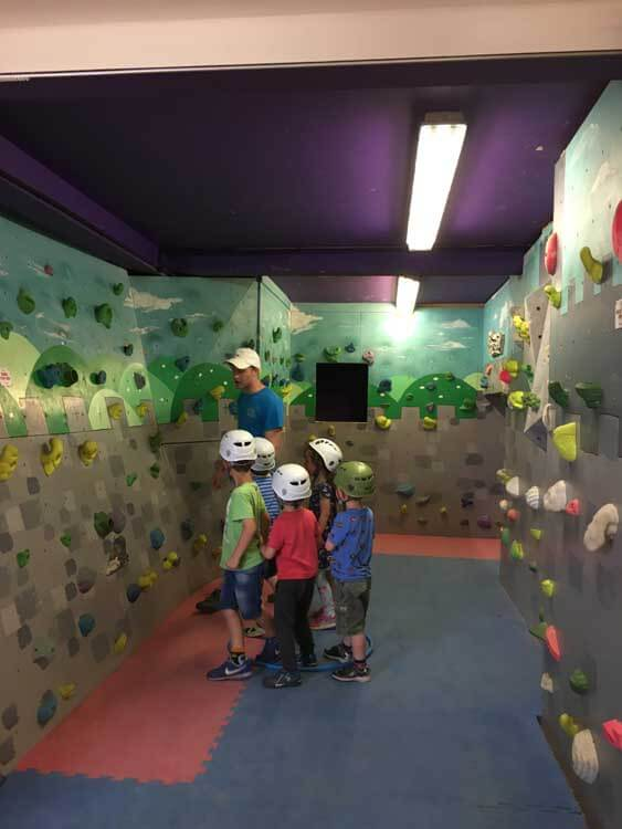 Children and instructor at indoor climbing wall in the Cotswolds