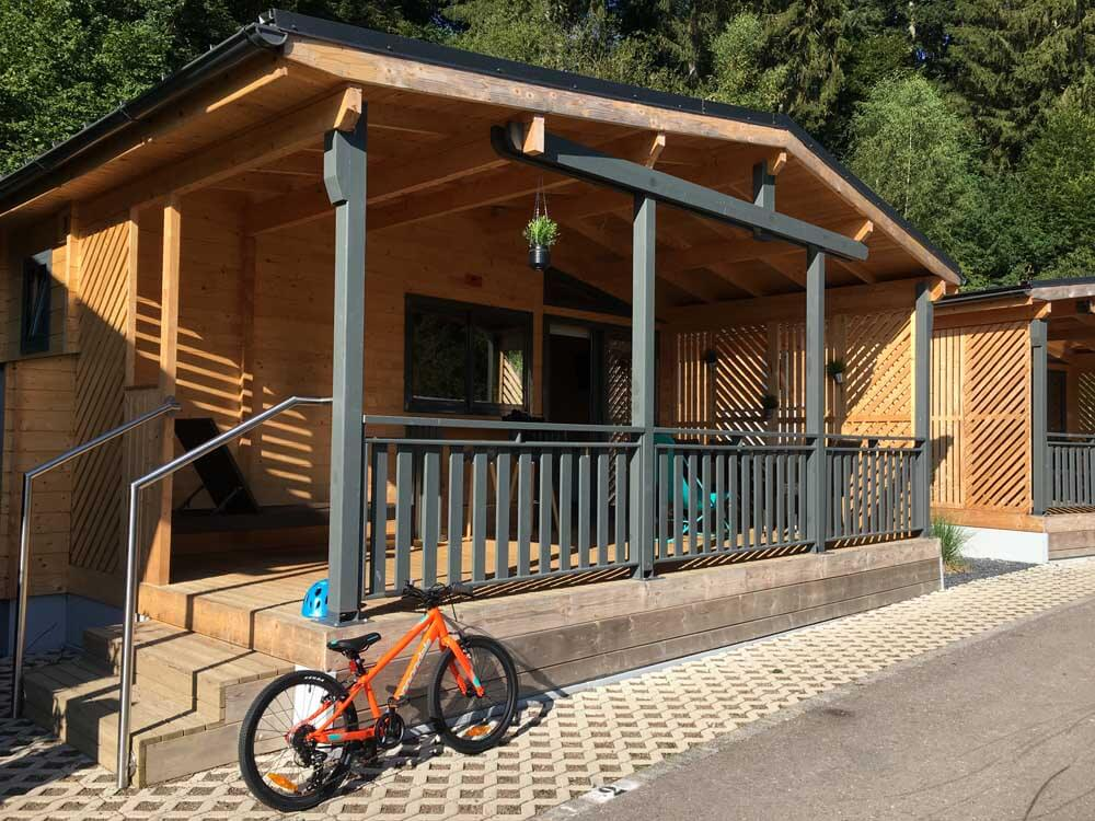bike parked outside chalet in luxembourg at Camping Kaul
