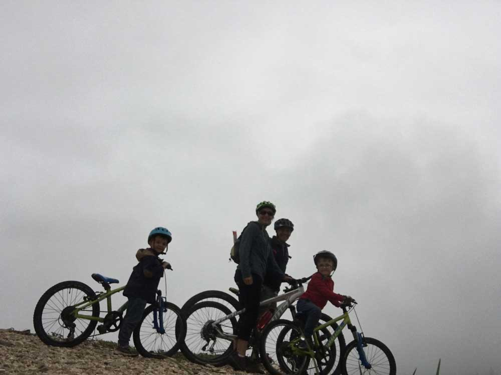 Family with bikes surrounded by mist, dolomites, italy