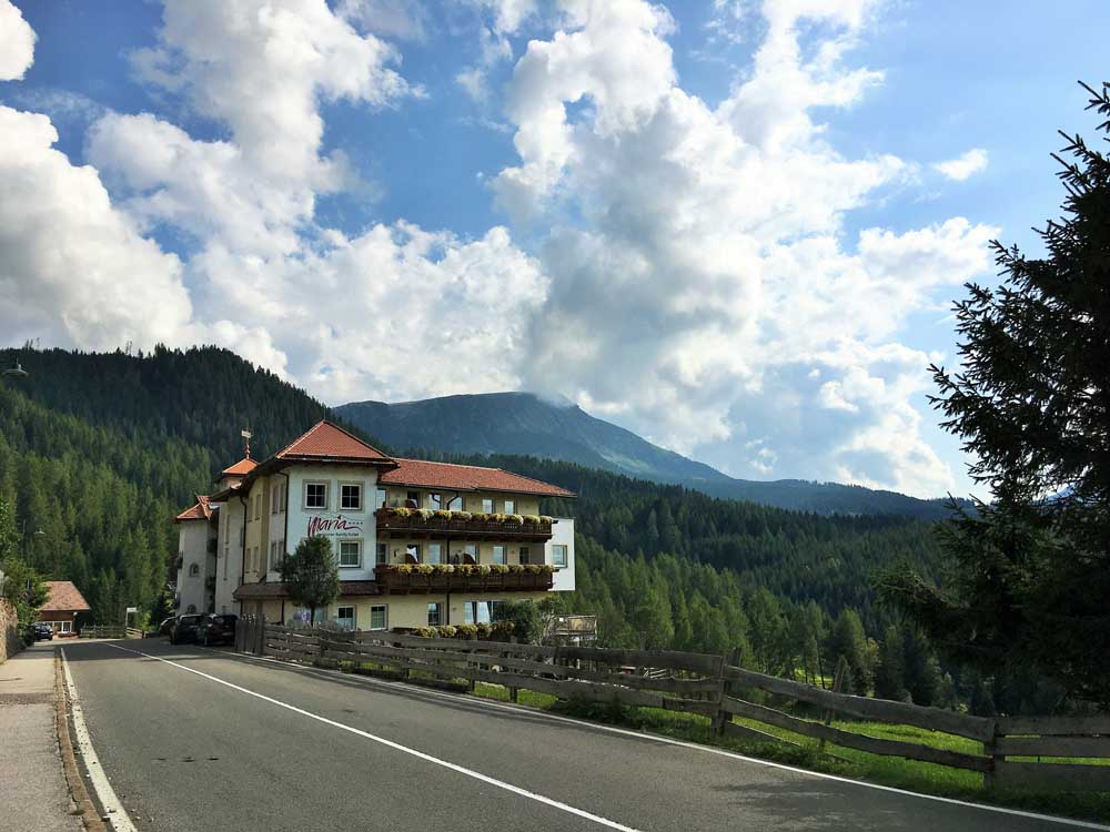 alpine hotel in dolomites italy beside road with trees in background