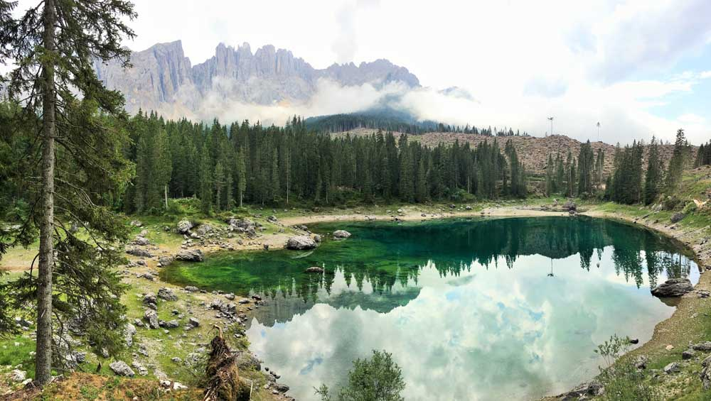 emerald alpine lake with trees and mountains, Lake Karersee with storm damage to the surrounding trees