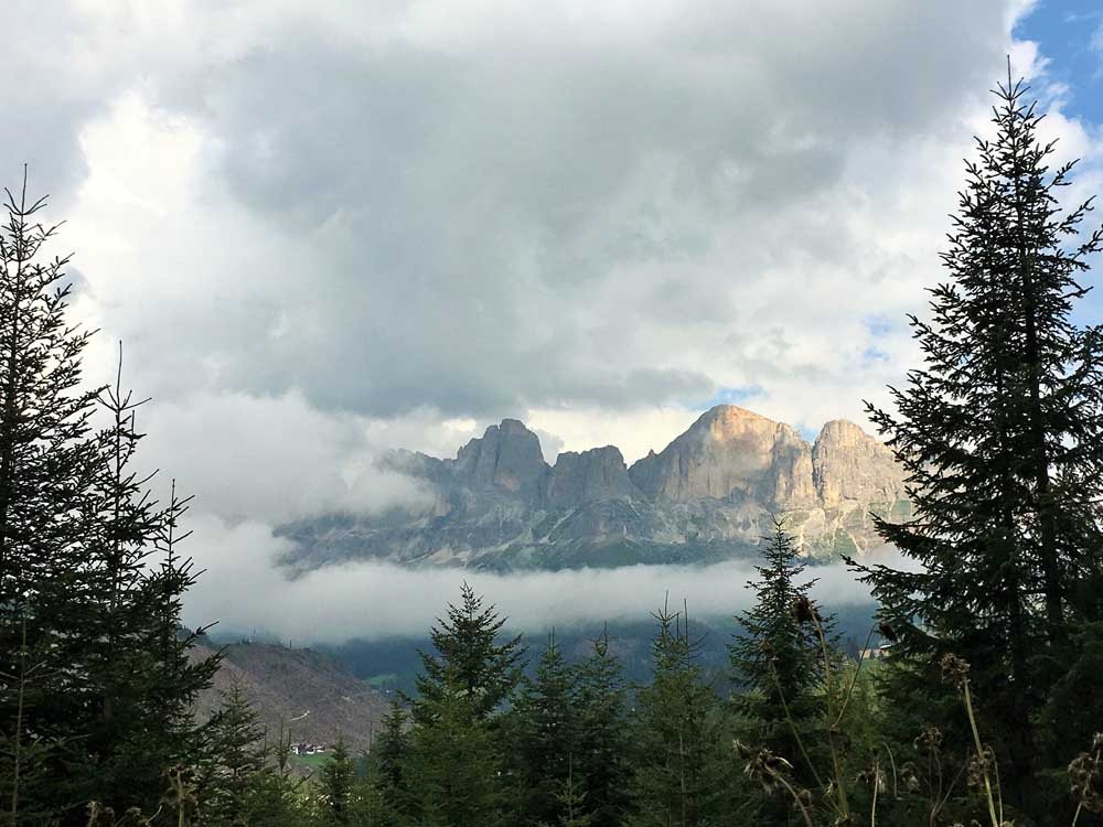 mountains surrounded by trees and clouds in the dolomites italy