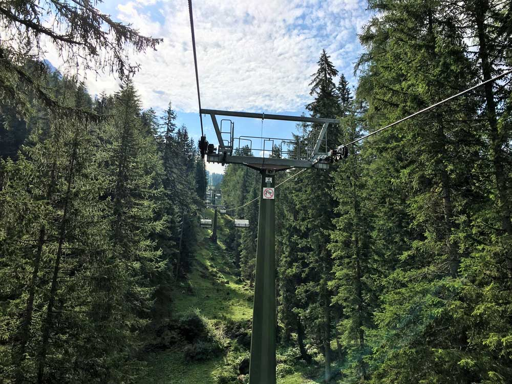 Oberholz chairlift surrounded by trees, dolomites with kids