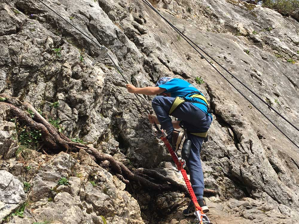 Child rockclimbing in the Dolomites Italy