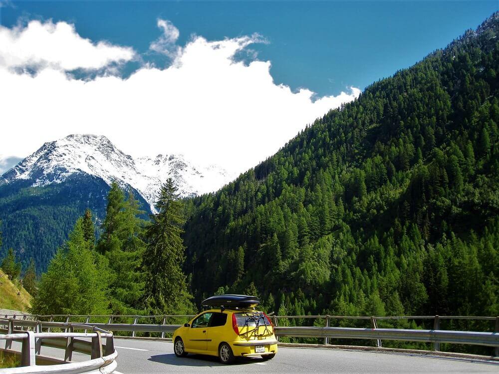 yellow car on mountain road