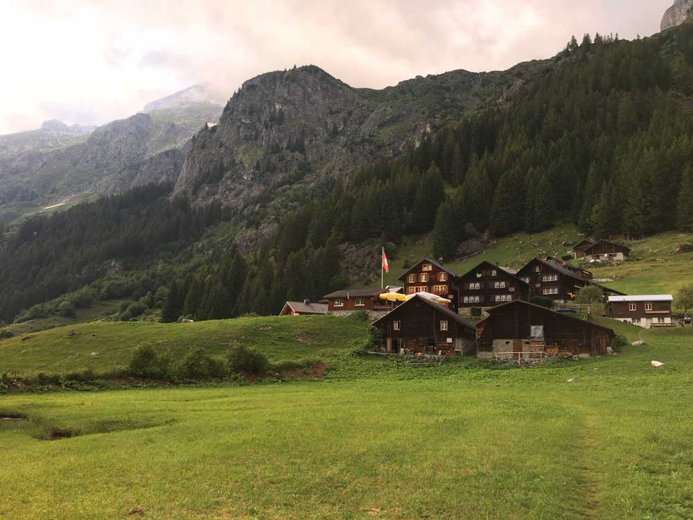 cloudy morning in the swiss alps with meadows and gasthaus golzernsee