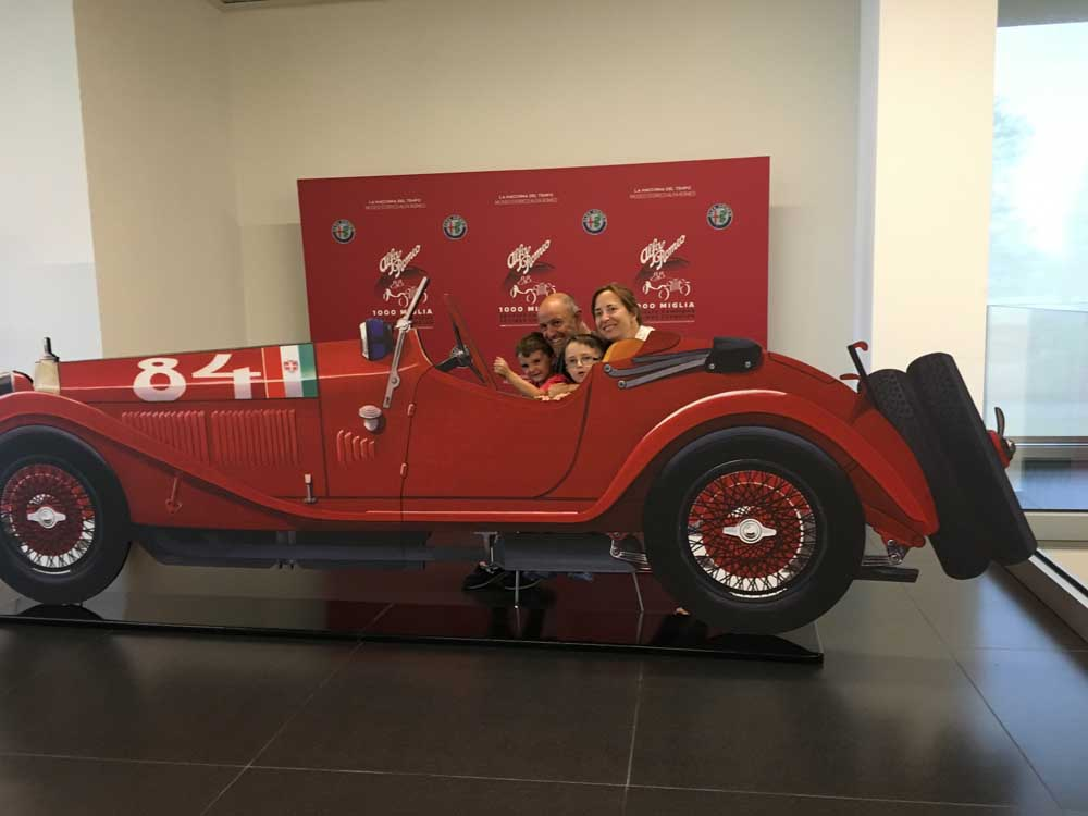 family posing in artificial car at Alfa Romeo Museum, northern Italy