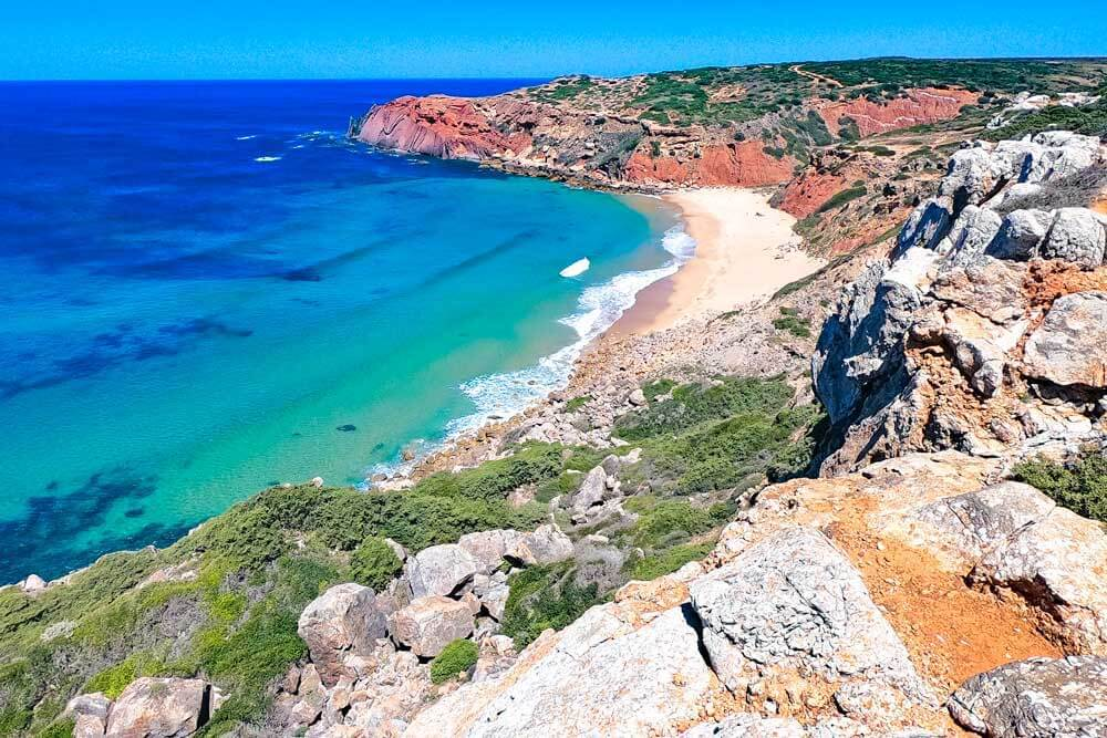 rocky viewpoint looking towards sandy beach, blue sea and red cliffs on the Fisherman's Trail in Portugal