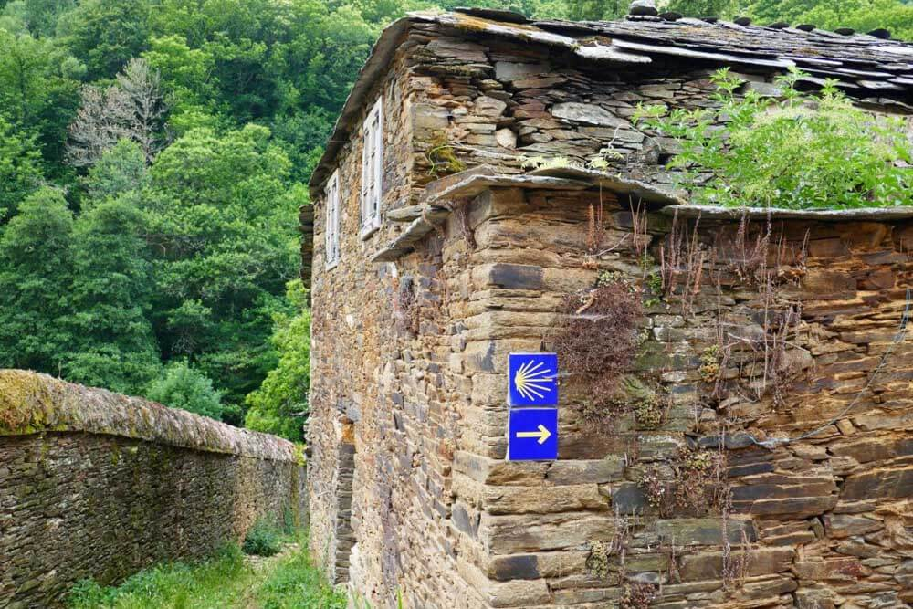 blue Camino waymarker on stone building, Spain