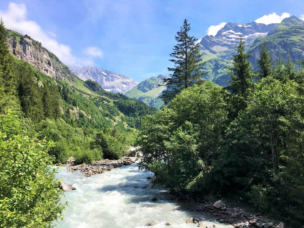 Chärstelenbach river with mountains, blue sky and forest, Maderanertal, Switzerland