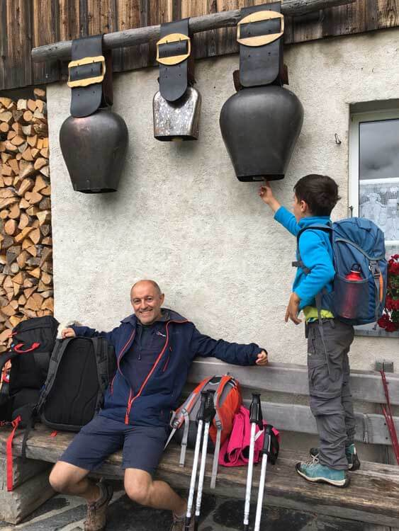 people rest at a diary with cow bells on the wall in the Swiss Alps
