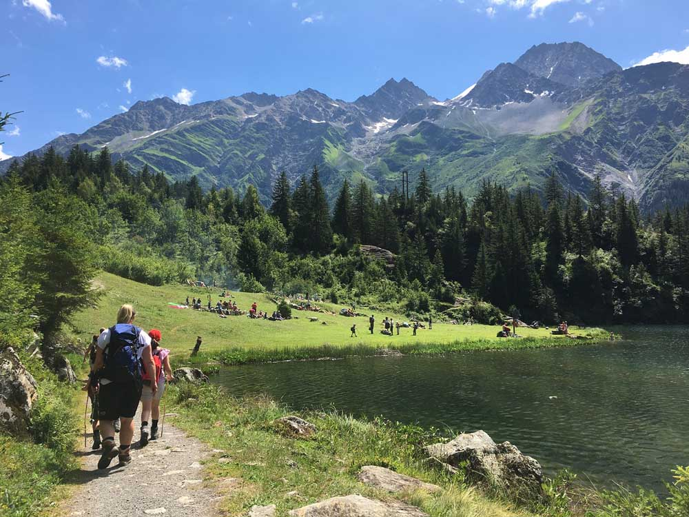 Hikers next to lake in Switzerland with mountains in background