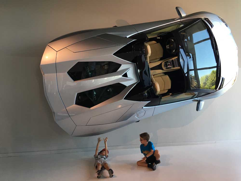 Silver car suspended on wall with children sitting underneath