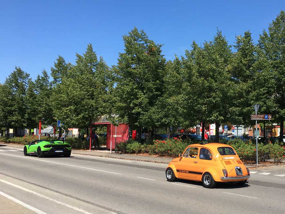 Orange Fiat 500 following green Lamborghini in Modena Italy, European family road trip from UK to Italy