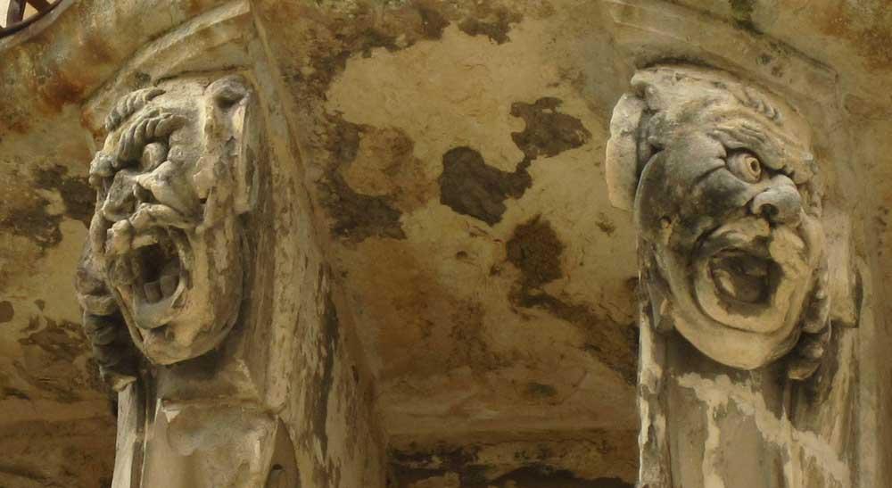 Gargoyles on a balcony in Noto Sicily