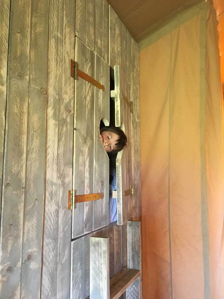 child looking out of cabin bedroom in glamping tent